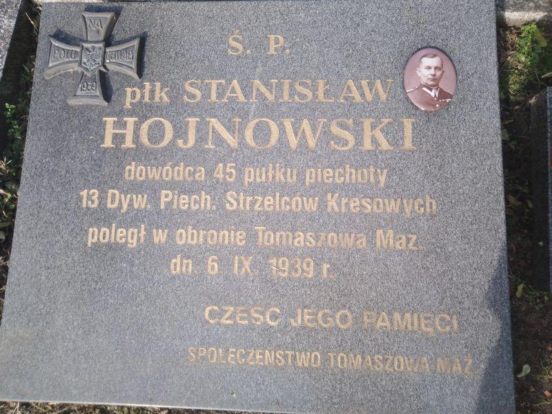 Na zdjęciu nagrobek płk Hojnowskiego, obrońcy Tomaszowa Mazowieckiego z 1939 roku. Widać płyte nagrobną, inskrypcję na nagrobku z datą urodzenia i śmierci pułkownika oraz z medalionem ze zdjęciem oficera