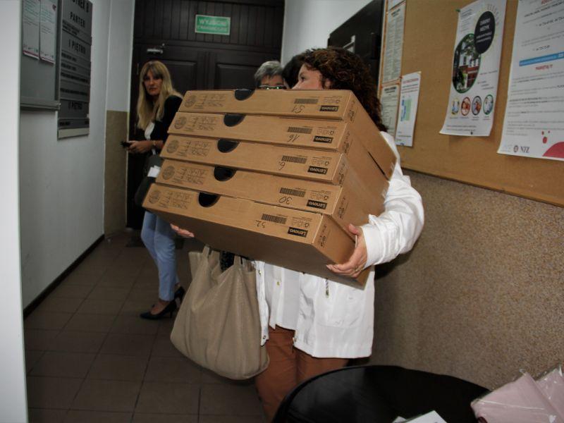 zdjecie przedstawia kobiet w białej kurtce trzymającą pięć opakowań z laptopami w oddali widać kolejne dwie kobiety oraz drzwi