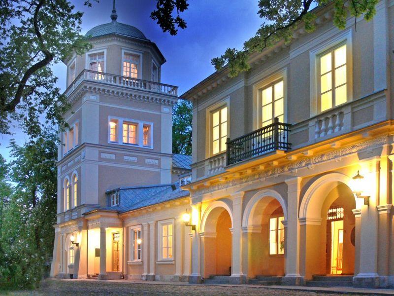 Na zdjęciu Budynek Muzeum w Tomaszowie Mazowieckim sfotografowany od frontu w godzinach wieczornych. Wewnątrz budynku zapalone światła oraz zapalone latarnie zewnętrznee